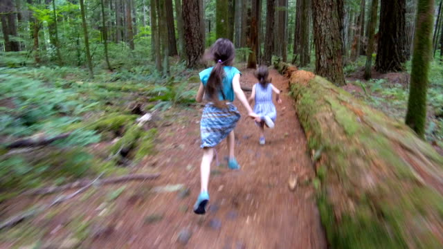 Sisters running through the forest follow cam