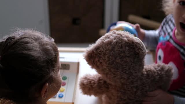 schwestern schülerinnen spielen geschäft in einem spielhaus in einer kleinkindschule - spielzeughaus stock-videos und b-roll-filmmaterial