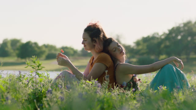vidéos et rushes de ws slo mo. sisters sit back to back in green field smelling wildflowers and daydreaming. - profil