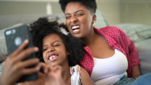 sisters taking a selfie sitting in the couch - sister stock videos & royalty-free footage
