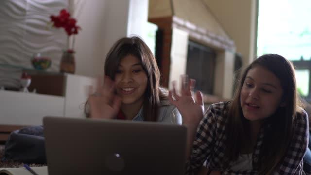 vídeos de stock, filmes e b-roll de irmãs falando em um laptop em aulas online em casa - distante