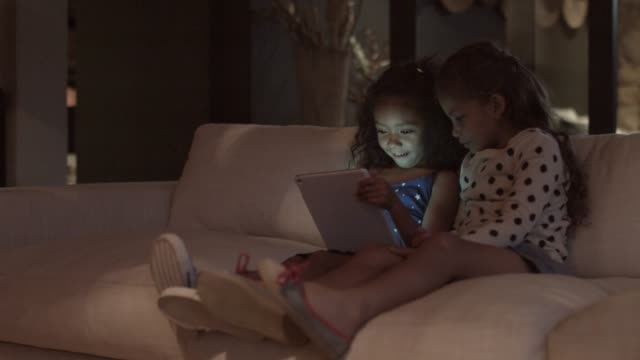 sisters using digital tablet at home - electrical equipment video stock e b–roll
