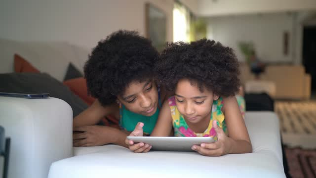 sisters using digital tablet together lying on the couch at home - e reader stock videos & royalty-free footage