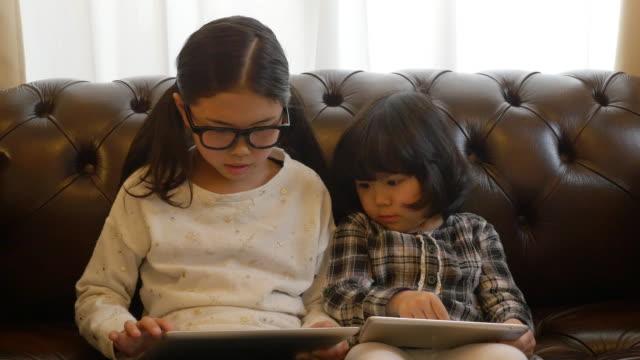 sisters using tablet on sofa moving slider right to left - legging stock-videos und b-roll-filmmaterial
