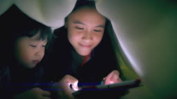 Sisters using tablet under the blanket