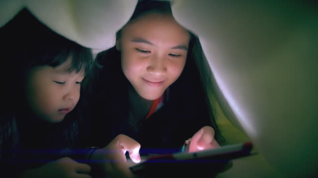 sisters using tablet under the blanket - childhood stock videos & royalty-free footage