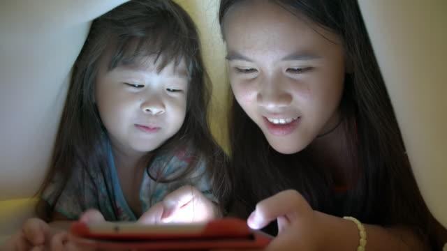 vidéos et rushes de sœurs à l'aide de tablettes sous la couverture - synthpop