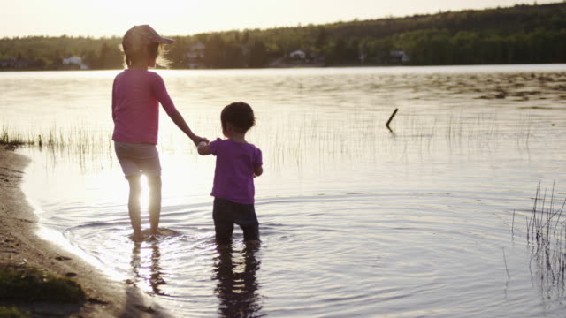 Hermanas infantil de agua en el lago al atardecer