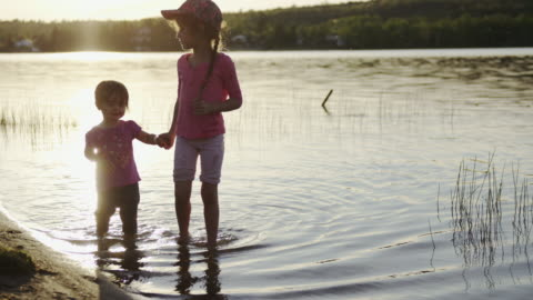sisters wading in the lake water at sunset - walking in water stock videos & royalty-free footage