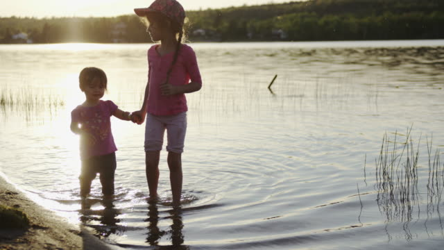 sisters wading in the lake water at sunset - exploration stock videos and b-roll footage
