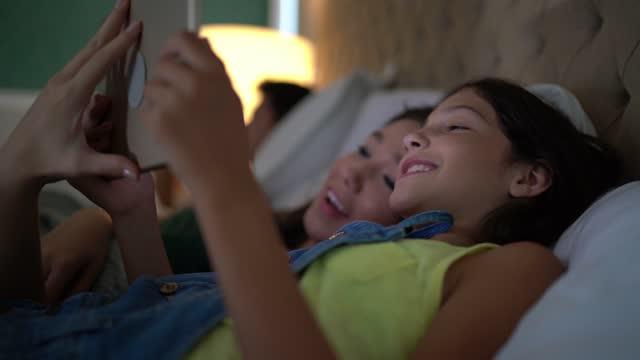自宅でベッドでデジタルタブレットで映画を見ている姉妹 - バイラルビデオ点の映像素材/bロール
