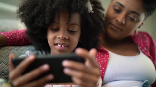 vídeos de stock, filmes e b-roll de irmãs que prestam atenção a algo no smartphone - telefone celular
