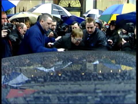 Sit Elton John clothes clearout ITN Elton John towards thru throng of press as helped into car by bodyguard PAN