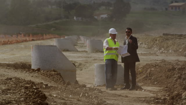 WS Site engineer with plans explaining construction site to businessman / Malaga, Andalusia, Spain