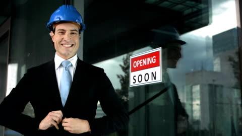vídeos y material grabado en eventos de stock de hd: gerente del centro posando junto a nuevo edificio - casco herramientas profesionales