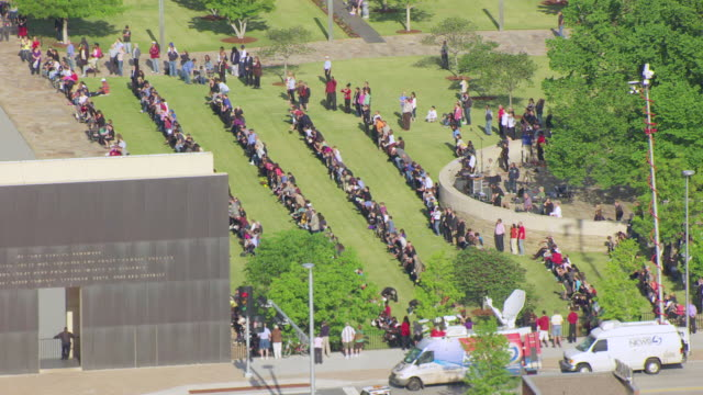 ws aerial sitting attendees stand up by reflecting pool during oklahoma city bombing remembrance ceremony / oklahoma city, oklahoma, united states - oklahoma city bombing stock videos & royalty-free footage