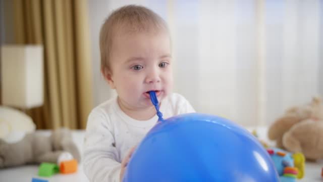 baby junge spielt mit blauen ballon sitzen - ein männliches baby allein stock-videos und b-roll-filmmaterial