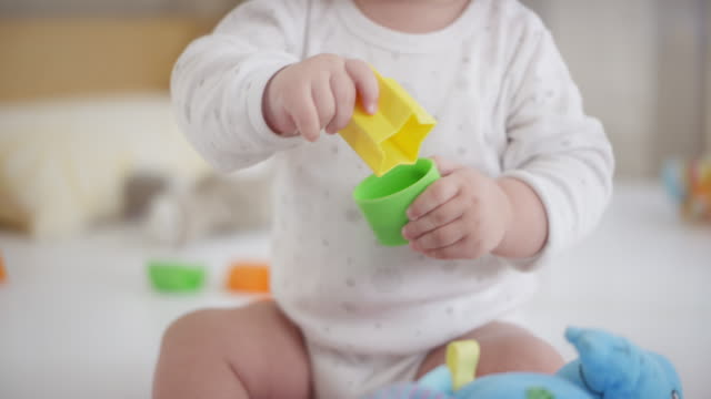 sitting baby boy playing with plastic shape blocks - man made stock videos and b-roll footage