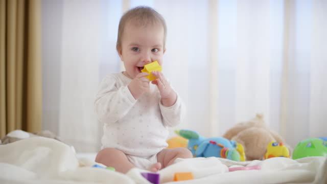 stockvideo's en b-roll-footage met baby jongen stellen vorm zit blokkeert in zijn mond - speelgoed