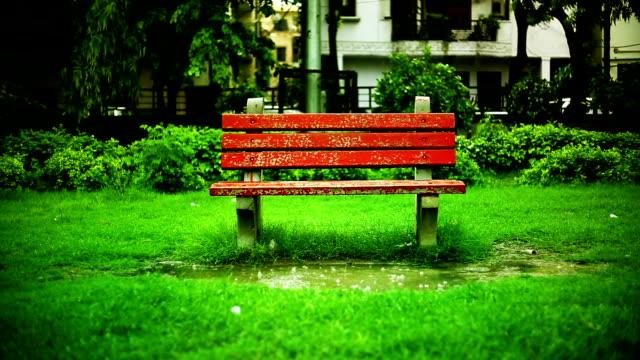 vídeos de stock e filmes b-roll de sitting bench in public park during rainfall - banco assento