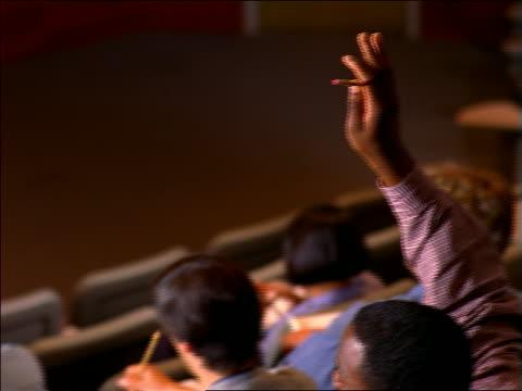 sitting black male student raising hand / pan to male professor in front of lecture hall talking - lecture hall bildbanksvideor och videomaterial från bakom kulisserna