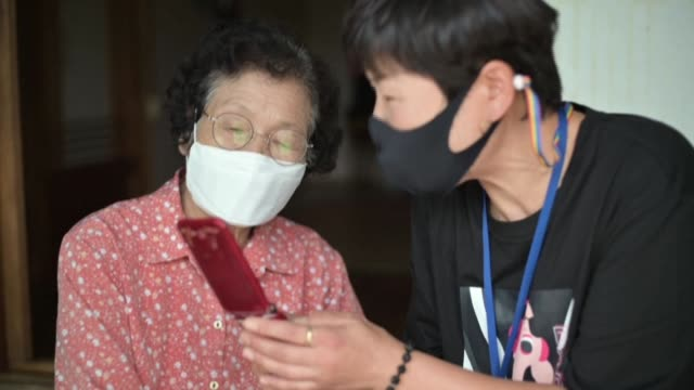 sitting in her tiny home, 83-year-old moon haeng-ja is struggling to master a new skill as the pandemic plays havoc with south korea's harvest... - korean new year stock videos & royalty-free footage