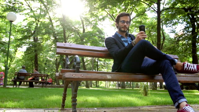 sitting in park and texting - bench stock videos & royalty-free footage
