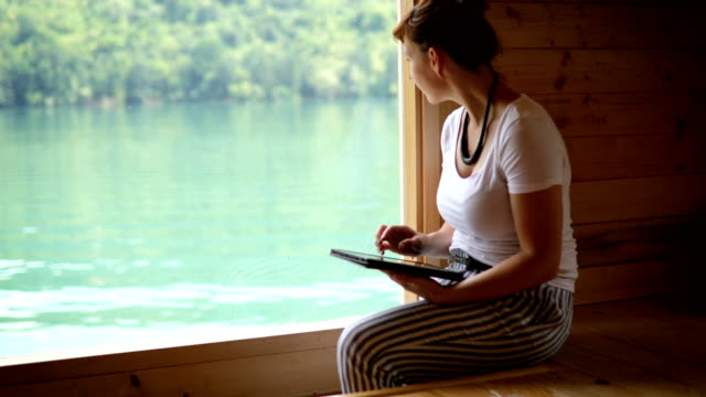 sitting next to the window in log cabin - stilt house - stilt house stock videos & royalty-free footage