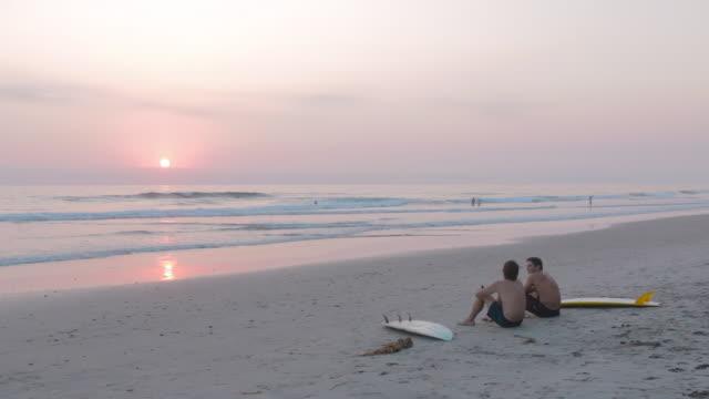 sitting on beach at sunset - badeshorts stock-videos und b-roll-filmmaterial