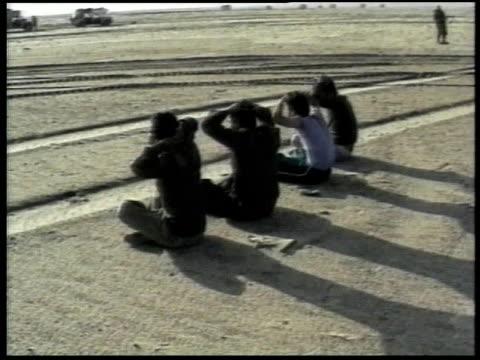 pows sitting on ground with hands over head military vehicles and guards in background - operation desert storm bildbanksvideor och videomaterial från bakom kulisserna