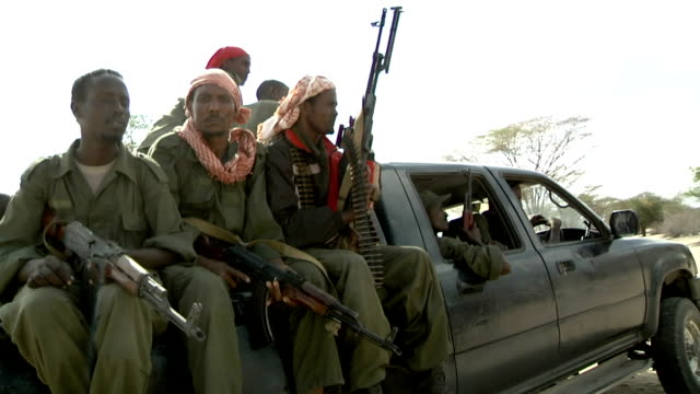 sitting on the back of a pickup truck and holding guns Somali militia men on July 31 2011 in Dhoobley Somalia