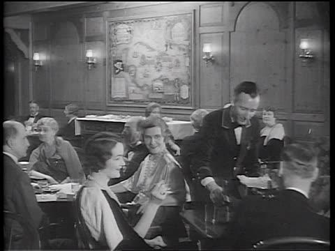 B/W 1934 sitting passengers talking + smoking in cruise ship smoking room