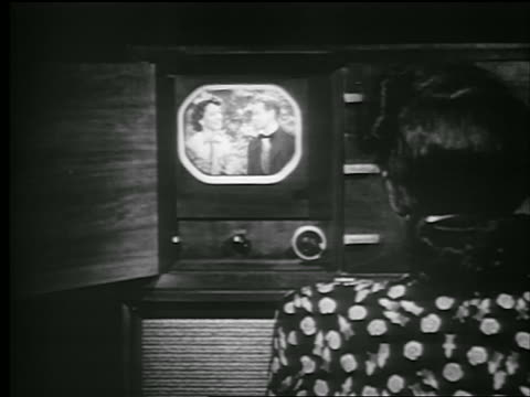 b/w 1948 rear view sitting woman watches television / man + woman on screen - 1948 stock-videos und b-roll-filmmaterial