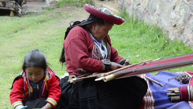 MS Sitting woman with child in traditional dress weaving yarn / Cuzco or Cusco, Peru