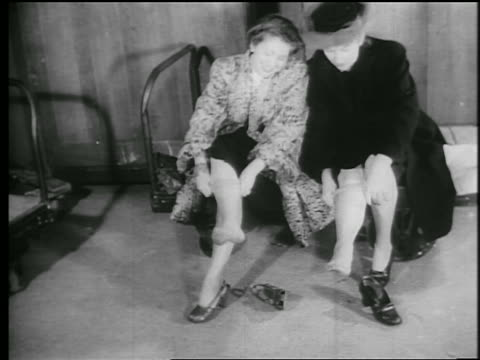 b/w 1945 2 sitting women pull nylons up their legs / educational - nylon stock videos and b-roll footage