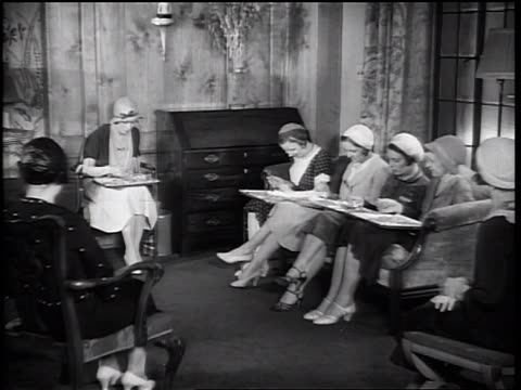 b/w 1933 sitting women sampling food from trays on their laps / woman handing tray to sitting woman - 1933 stock videos and b-roll footage