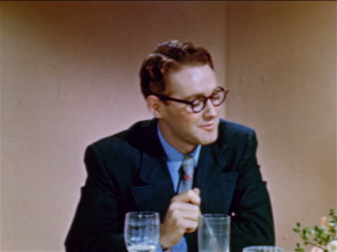 vídeos y material grabado en eventos de stock de 1952 sitting young man with glasses talking to someone off screen / industrial - 1952