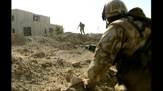 total death toll passes 400 tx iraq near basra ext armed british troops running towards building - bassora video stock e b–roll