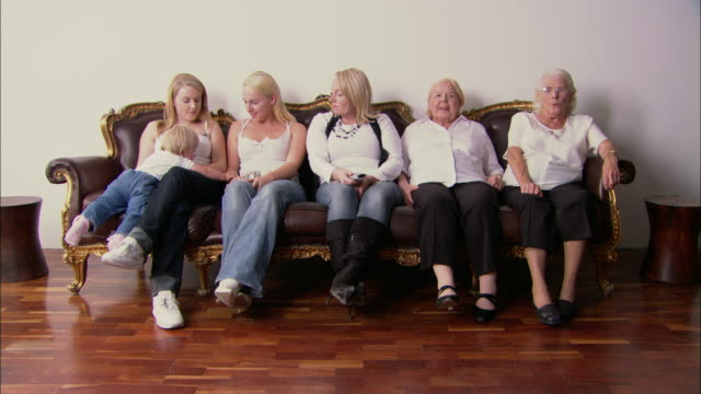 ws six females, from baby to great granny, sitting on sofa/ women get up and leave on by one/ england - großmutter stock-videos und b-roll-filmmaterial