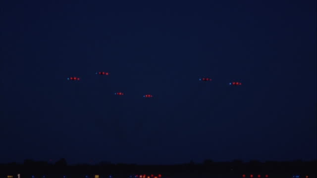 six fighter planes fly in formation through the night sky. - jagdflugzeug stock-videos und b-roll-filmmaterial
