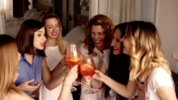 Six girls standing in a close circle and communicating. Celebrating, drinking beverages from glasses. Cheers. Indoors. Bright, fancy interior. High angle footage