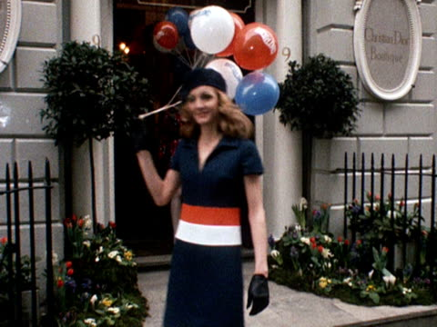six models walk out of the london christian dior boutique carrying balloons and wearing dresses and coats designed by jorn langberg for dior 1968 - cappello video stock e b–roll