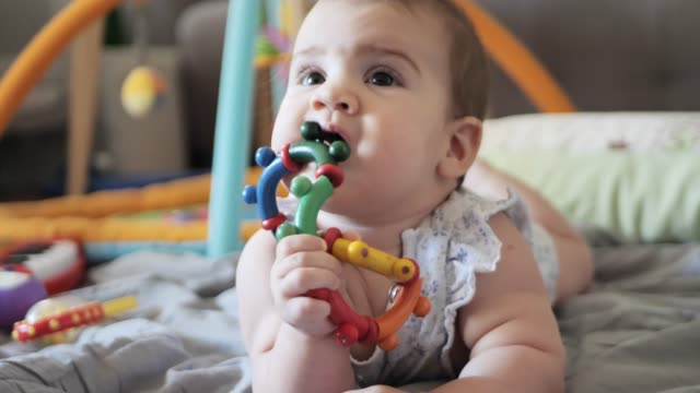 six month old baby girl biting her wooden toy - only baby girls stock videos & royalty-free footage