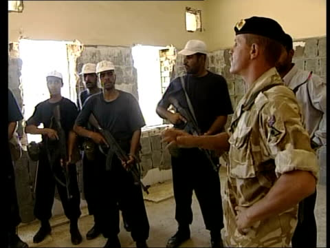 six months since fall of regime bv iraqi policemen taking cover next wall as trying to catch armed robbers pan truck driven along by robbers officers... - military exercise stock videos and b-roll footage