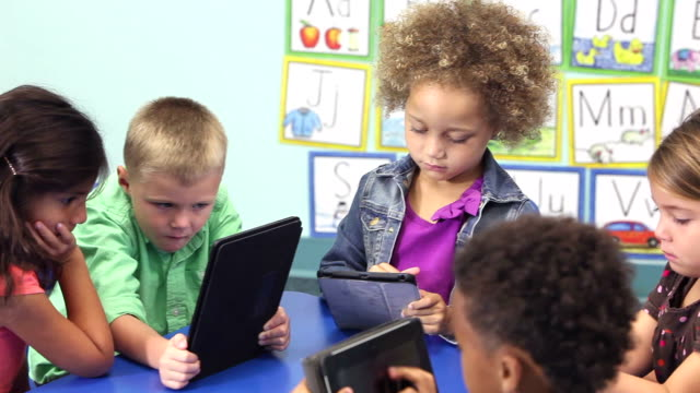 six multi-ethnic children in schiool using digital tablets - preschool stock videos & royalty-free footage