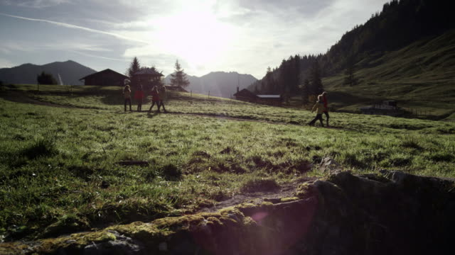 six people walking a mountain path und jump, meadow, pan shot, sun, distance shot - cottage stock videos & royalty-free footage