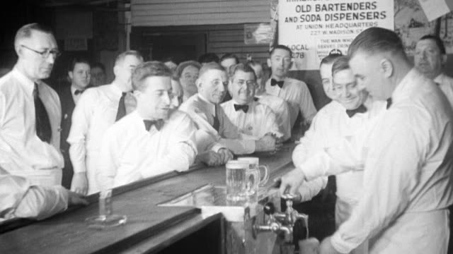 Six well dressed bartenders put on aprons in preparation for training / CU sign stating 'initiation and test of the old bartenders and soda...