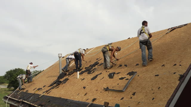 vidéos et rushes de ms six workers removing nails at top of roof / chelsea, michigan, united states - couvreur