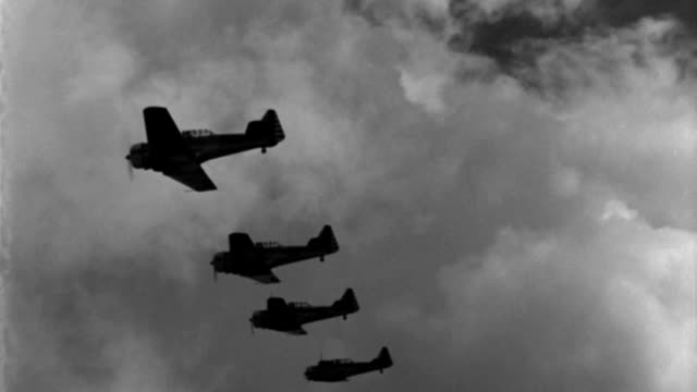 six wwii advanced trainer aircraft fly in close formation in a cloudy sky. - formationsfliegen stock-videos und b-roll-filmmaterial