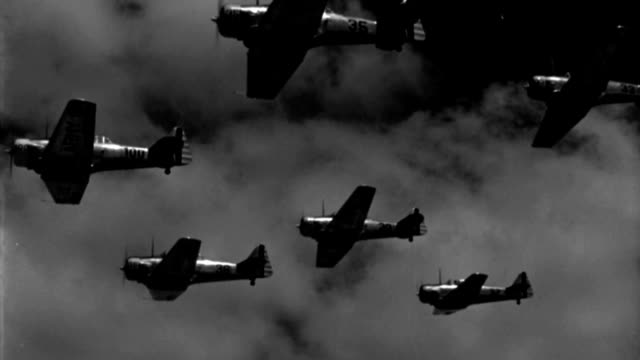 six wwii advanced trainer aircraft fly in close formation. - formationsfliegen stock-videos und b-roll-filmmaterial
